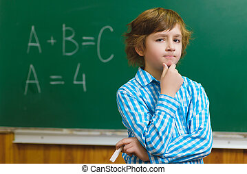 boy thinking on blackboard background . Educational and school concept