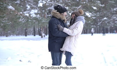 Young beautiful couple hug in winter forest