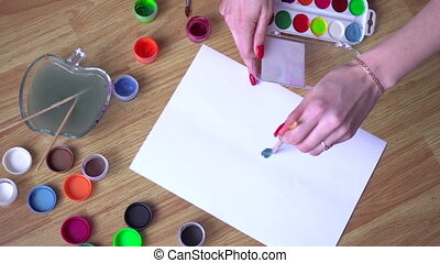 girl draws a brush on paper with bright colors top view