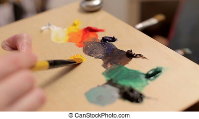 Artist Mixing Oil Colors On A Palette