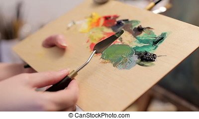 Applying Oil Colors On Palette in painter studio