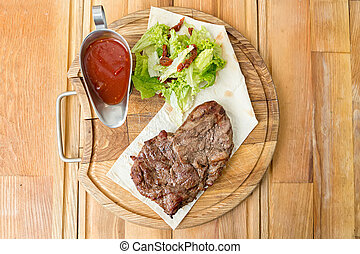 cooked steak on a wooden board - cooked steak on a pita, a...