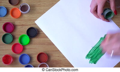 the artist draws a green paint on a sheet of paper time laps