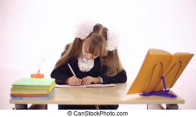 Schoolgirl sitting at school desk - A girl dressed in a...
