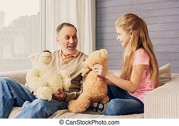 Cheerful girl and grandparent having fun with toys - Happy...