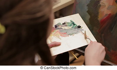Artist painting in her shop