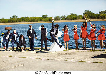 Groom jumps behind a bride while they stand together with friends on the estuary shore