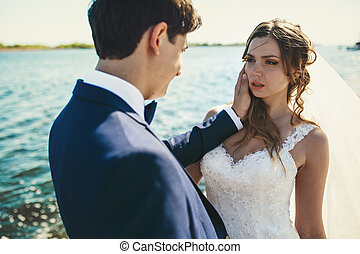 Bride looks at a groom seductivly posing by the sea