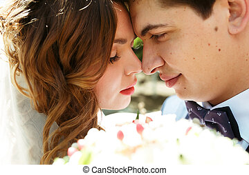 Perfect newlyweds' faces touch before a wedding bouquet
