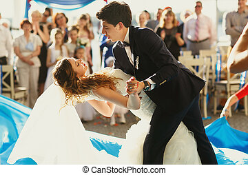 Groom bends bride over during their first dance outside in a...