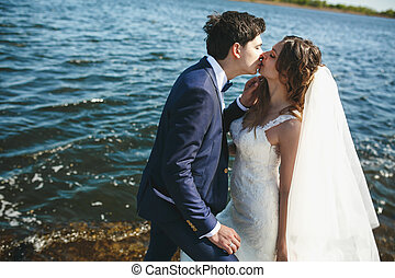 Fiance kisses bride tenderly standing with her by the sea