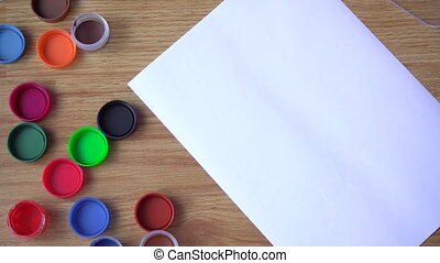 the artist draws a green paint on a sheet of paper closeup