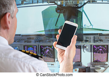 Airline pilot using smart phone - Airline pilot wearing...