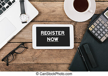 Register Now text on tablet computer on office desk -...
