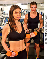 Couple together gym. Friends workout with fitness equipment....
