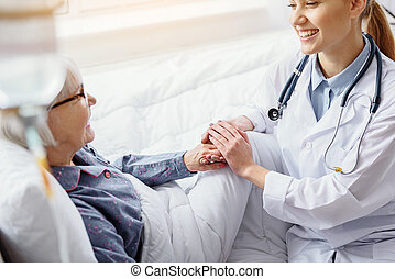 Smiling patient keeping hand of doctor - Happy old woman are...