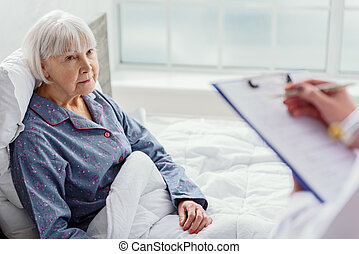 Physician questioning old woman in hospital - Doctor asking...