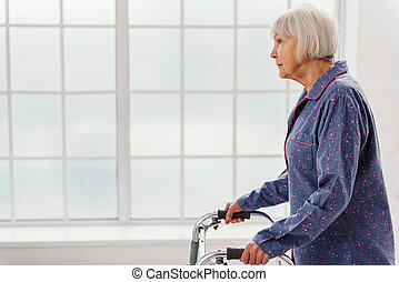 Serene grandmother going with walking frame in hospital -...