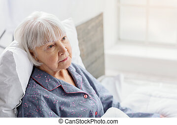 Female retiree lying in bright apartment of clinic -...