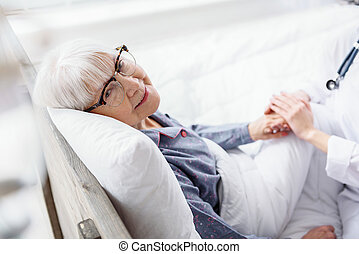 Cheerful old woman situating in cot in hospital - Outgoing...