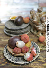 Lychees and Passion Fruit or Maracuya on wooden background -...