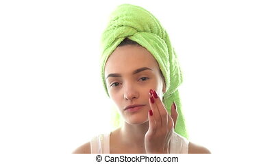 young girl with towel on the hair causes the cream to the...