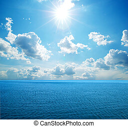 sea - cloudy blue sky above a surface of the sea