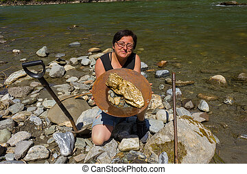 Gold Nugget mining from the River, with a gold pan, and find...