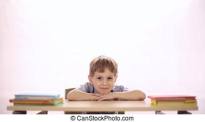 Funny boy sitting at school desk