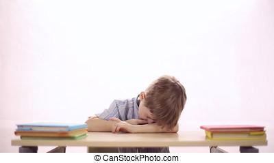 Funny boy sitting at school desk - Funny four-year boy...