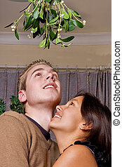 Oops mistletoe - Young couple has just noticed they are...