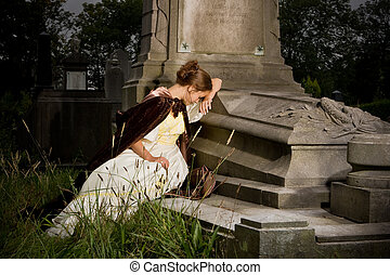 Mourning on a tomb - Young woman in victorian dress mourning...