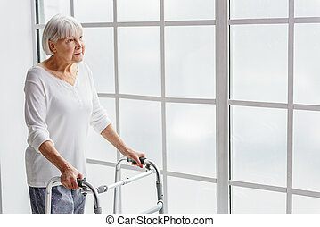 Smiling retiree holding walking aid in her hand - Outgoing...