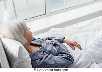 Serene old woman lying on cot in hospital apartment - Calm...