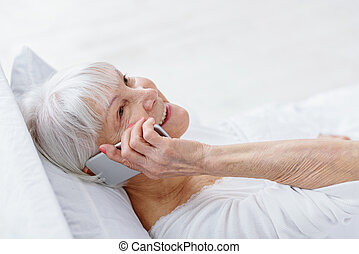 Outgoing female pensioner speaking by phone - Cheerful old...