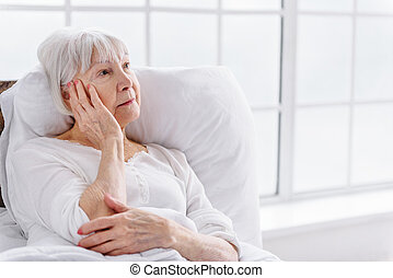 Worried patient reclining in cot at clinic - Distressed old...