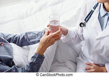 Therapeutic holding out drink to patient in clinic - Young...
