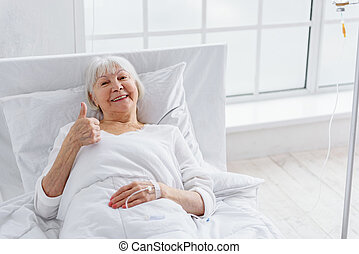 Cheerful old woman is on drop glass in clinic - Smiling...
