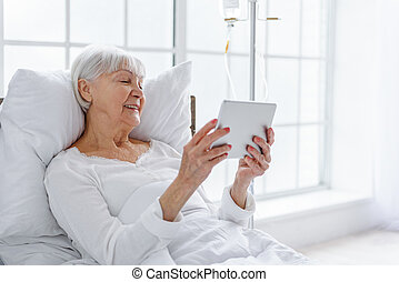 Smiling retiree looking at digital tablet in clinic - Happy...