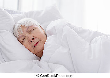 Serene old woman keeping to bed in hospital - Self-possessed...