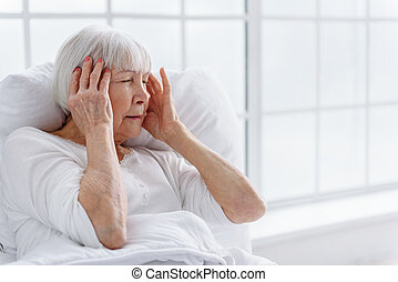 Worried old woman has headache in hospital - Distressed...