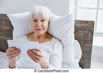 Cheerful granny keeping her tablet in hospital - Outgoing...
