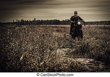 Young, stylish man on vintage custom racer in field.