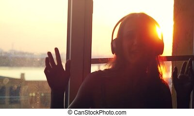 Young daydreaming woman sitting by the window wears headphones through the sun listen to music during amazing sunset with lense flare effects.