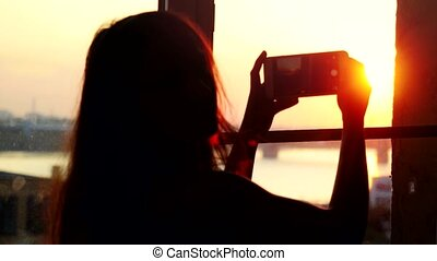 Young woman taking photos of city with blurred architectures...