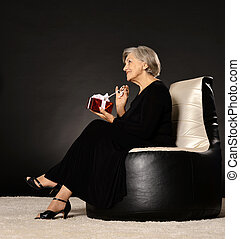 Happy elderly woman sitting with gift on black armchair