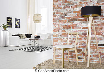 Functional loft with brick wall, black lamp and white sofa