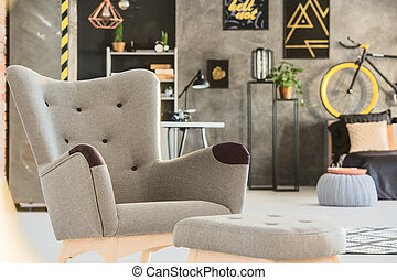 Grey room with stylish upholstered chair and pouf