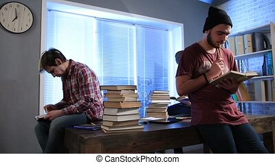 Male students doing research with books in library