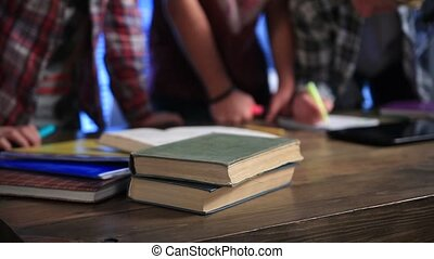 Cropped view of students writing in exercise books - Closeup...